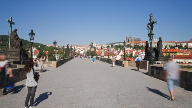 Pedestrians cross the Charles Bridge in Prague.