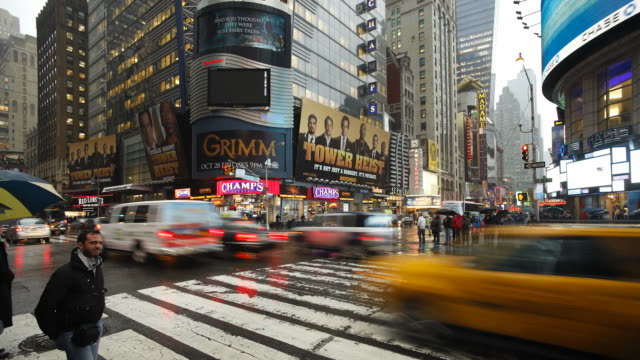 pedestrians cross the intersection of 42nd street in times square on a rainy day. - large scale screen stock videos & royalty-free footage