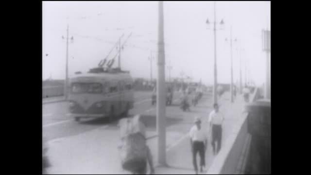 Pedestrians cross the Kototoi-bashi as a trolley bus heads traffic traveling beside them.