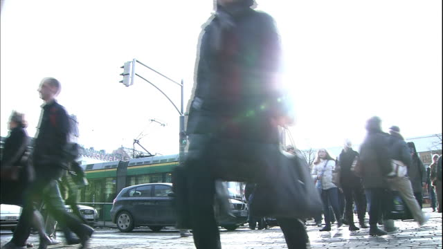 pedestrians cross the street at a busy intersection. - road junction stock-videos und b-roll-filmmaterial