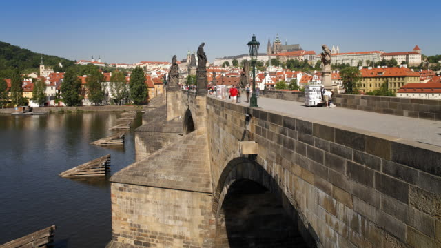 pedestrians cross the the famous charles bridge in prague. - charles bridge stock videos and b-roll footage