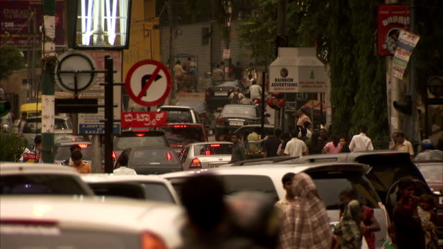 pedestrians cross through traffic on a busy street. - bangalore stock videos and b-roll footage