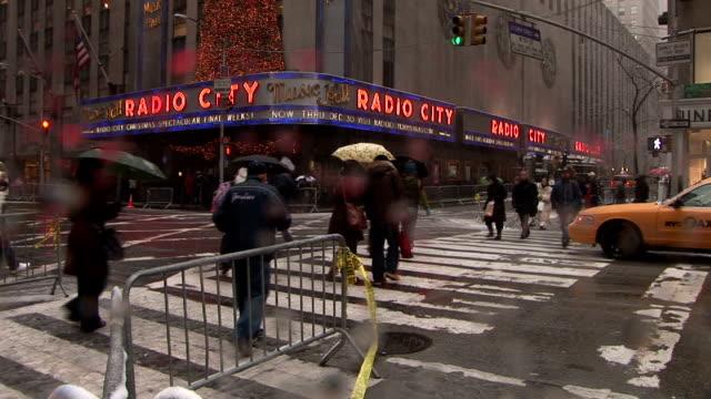 stockvideo's en b-roll-footage met pedestrians crossing 6th avenue by radio city music hall during snow storm manhattan - radio city music hall