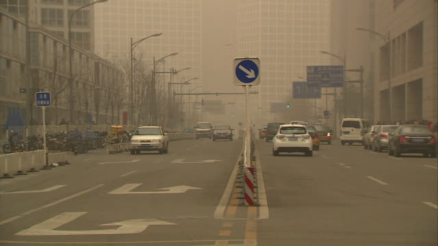 pedestrians crossing a city street in beijing, china on a smoggy day. - smog stock videos & royalty-free footage