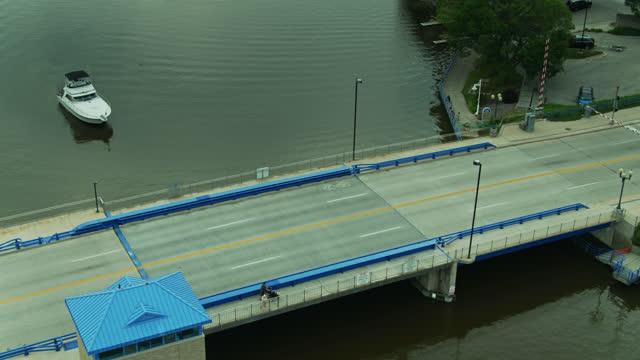 pedestrians crossing bridge as boat waits - aerial - bascule bridge stock videos & royalty-free footage