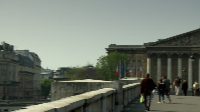 ms pan pedestrians crossing bridge towards national assembly, paris, france - french national assembly stock-videos und b-roll-filmmaterial