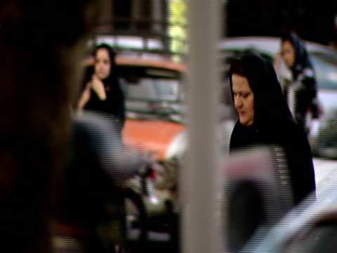 vidéos et rushes de pedestrians crossing busy city street, traffic passing by / tehran, iran - format vignette