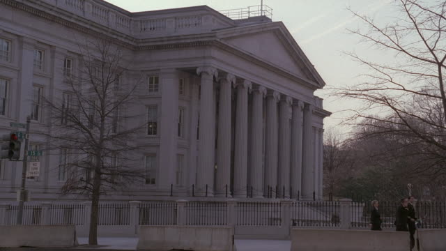 la pedestrians crossing by front of u.s. treasury building past columns and van driving by / washington, d.c., united states - 財務省ビル点の映像素材/bロール