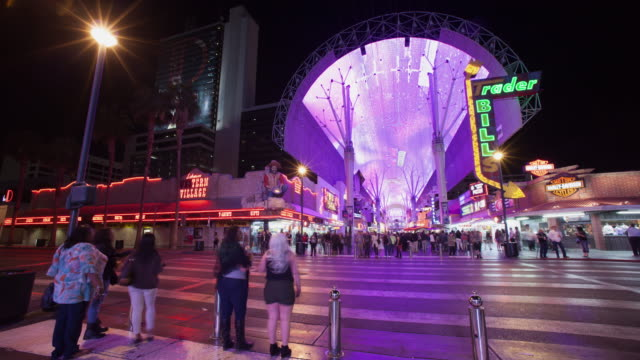WS T/L PAN Pedestrians crossing Fremont Street at night / Las Vegas, Nevada, United States