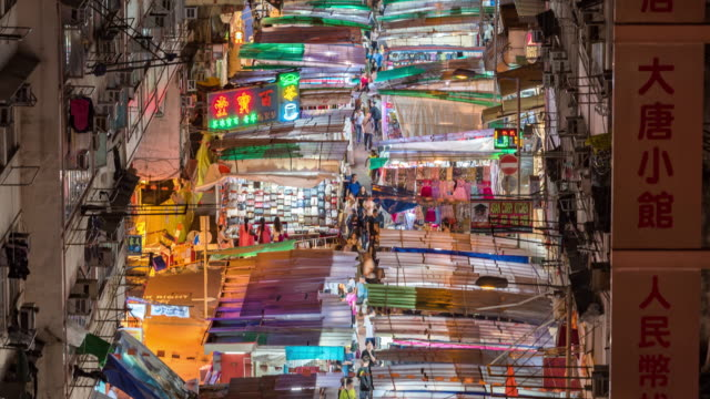 pedestrians crossing intersection in temple street night market, crowd people are walking a market at night - crossing stock videos & royalty-free footage