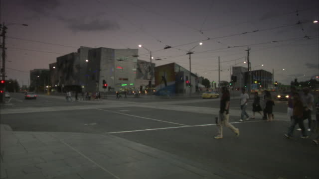 WS Pedestrians crossing road intersection with Federation Square in background, Melbourne, Victoria, Australia