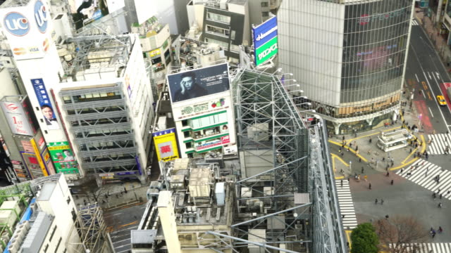 pedestrians crossing street at shibuya intersection aerial view - shibuya station stock videos and b-roll footage
