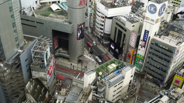 pedestrians crossing street at shibuya intersection aerial view - crossroad stock videos & royalty-free footage