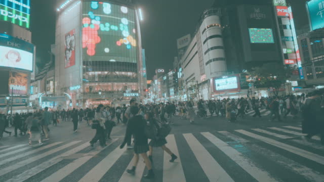 pedestrians crossing street at shibuya intersection - shibuya station stock videos and b-roll footage