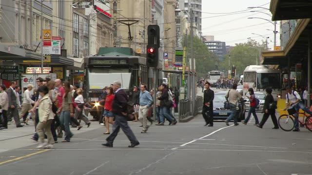 ws pedestrians crossing street at signal / melbourne, victoria, australia - 横断する点の映像素材/bロール