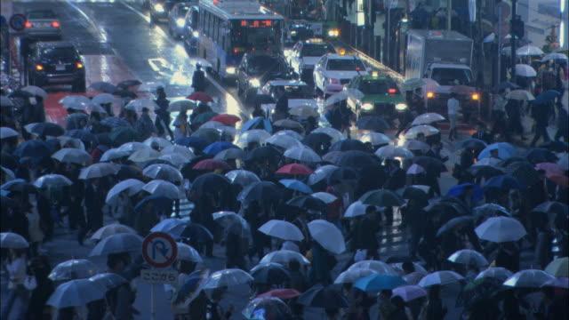 WS Pedestrians crossing street corner during rain / Tokyo, Honshu, Japan