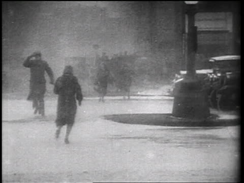 b/w 1935 pedestrians crossing street in windy snowstorm / educational - 1935 stock videos & royalty-free footage