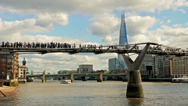 pedestrians crossing the millennium bride across the river thames in london, uk - london millennium footbridge stock videos & royalty-free footage