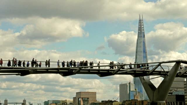 pedestrians crossing the millennium bride across the river thames in london, uk - shard london bridge stock videos & royalty-free footage