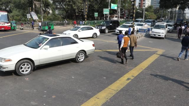 pedestrians crossing the road at the city's banani in dhaka amid moving vehicles - 交通事故点の映像素材/bロール