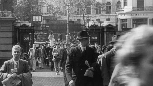 1951 MONTAGE Pedestrians crossing the street of a crowded city square on their daily commute / United Kingdom