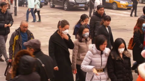 pedestrians crossing the street, some wearing smog masks, in beijing, china. - smog stock videos & royalty-free footage