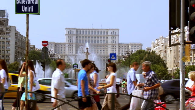 ms pedestrians crossing union square near house of people / bucharest, romania - romania stock videos & royalty-free footage