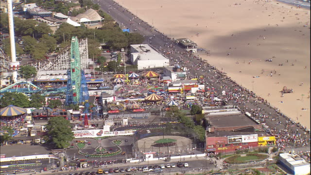 pedestrians crowd a boardwalk near a beach and astroland and deno's wonder wheel park in new york. - coney island brooklyn stock videos & royalty-free footage