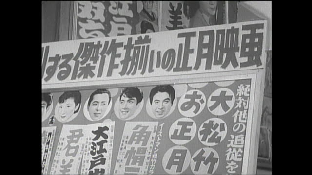 pedestrians crowd a busy market street; movie posters hang in a market in postwar japan. - 1950~1959年点の映像素材/bロール