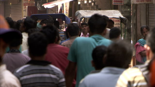 pedestrians crowd a market street in delhi. - delhi stock videos & royalty-free footage