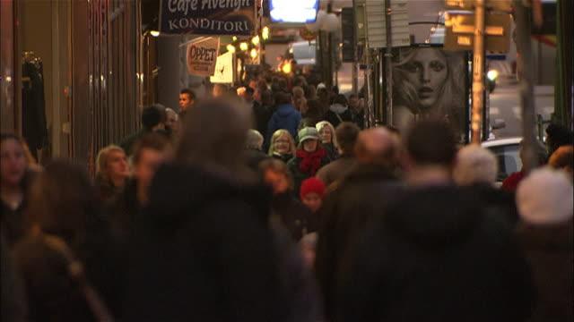 Pedestrians crowd a sidewalk in a commercial area in Stockholm, Sweden.