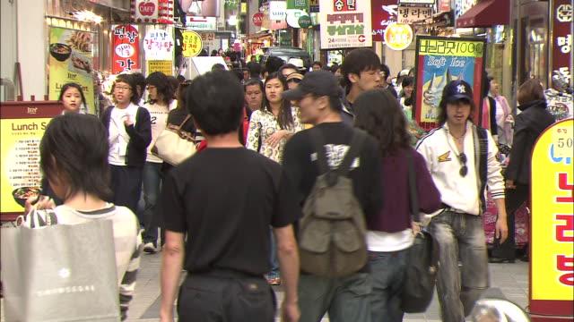 stockvideo's en b-roll-footage met pedestrians crowd the streets of downtown seoul. - winkelbord