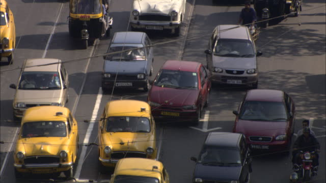 pedestrians dodge automobiles in a calcutta traffic jam. - kolkata stock videos & royalty-free footage