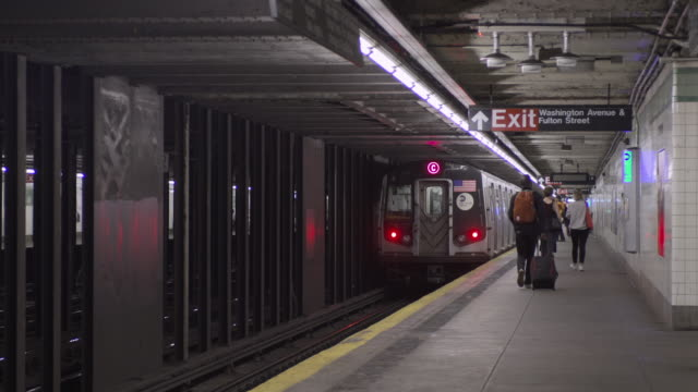 pedestrians enter and exit subway train on its way to manhattan from brooklyn. - exit sign stock videos & royalty-free footage