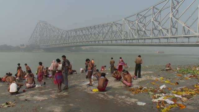 pedestrians gather on a ghat at hooghly river near howrah bridge in calcutta. - howrah bridge stock videos and b-roll footage