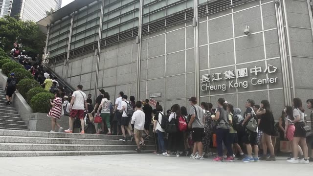 stockvideo's en b-roll-footage met pedestrians holding umbrellas walk past signage for the cheung kong center building in hong kong china on saturday july 29 2017 pedestrians pass in... - hongkong eiland
