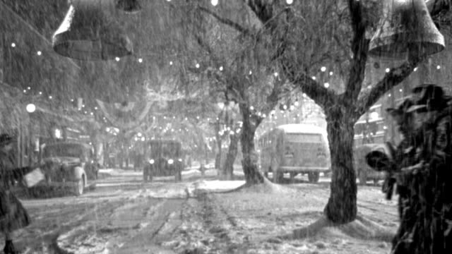 pedestrians hurry through heavy snow on a small town main street decorated for christmas. - 1946 stock videos & royalty-free footage