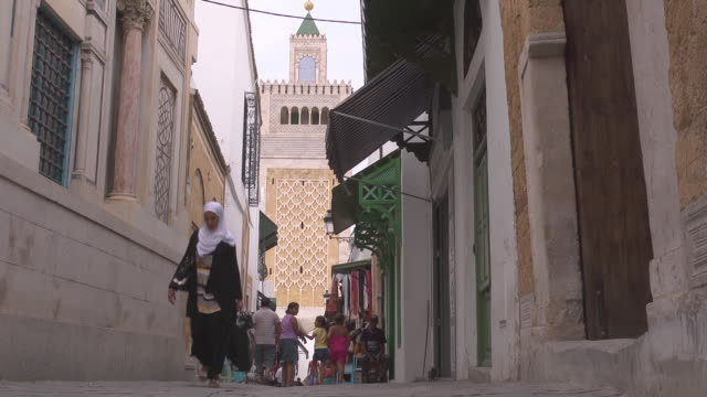 pedestrians in an alley  in front of the ez-zitouna mosque - tunisia video stock e b–roll