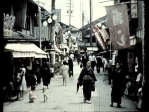 vídeos de stock, filmes e b-roll de ws ms pan pedestrians in ancient city streets, buddhist monk wearing strange mask playing flute, two ceremoniously garbed temple maidens approach kasuga (shinto) shrine / nara, japan / audio - 1951