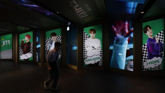 vidéos et rushes de pedestrians in face masks walking past advertisement of south korean boy band bts displayed at a subway station, in seoul, south korea, on friday,... - k pop