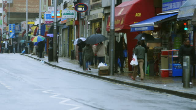 WS PAN Pedestrians in street of Peckham on rainy day / London, England, United Kingdom