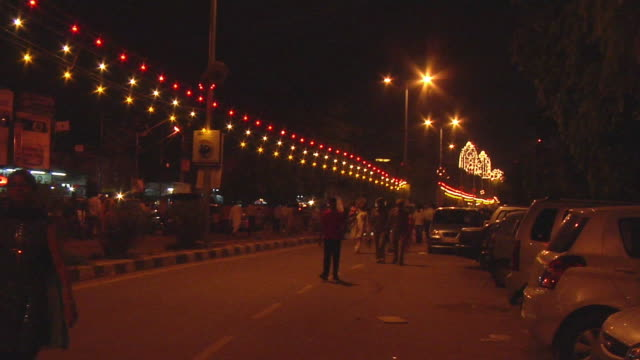 WS Pedestrians in street with decoration illuminated at night / Delhi, India