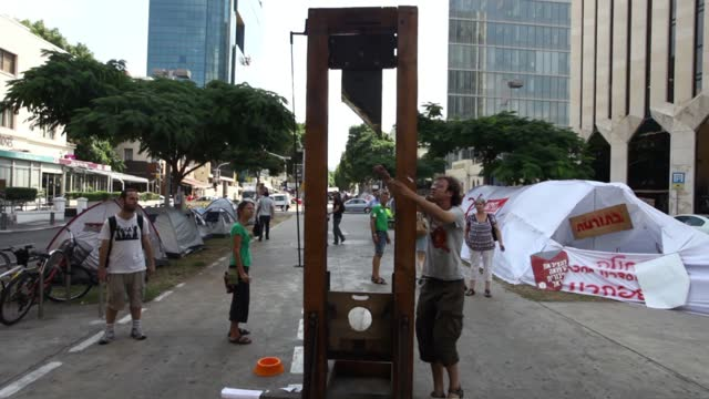 "pedestrians inspect a guillotine installation, the symbol of the french revolution placed by demonstrators at the ""tent city"" social protest compound... - execution by guillotine stock videos & royalty-free footage"