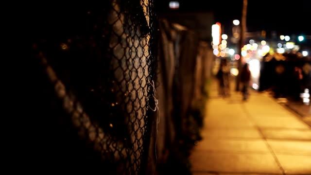 pedestrians loiter on a dark street. - gang stock videos & royalty-free footage