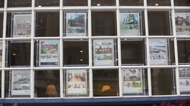 pedestrians look at residential homes advertised in the window on an estate agent in the putney district of london advertisements for properties for... - for sale englischer satz stock-videos und b-roll-filmmaterial