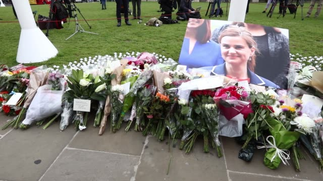 pedestrians look at tributes left to jo cox a british parliamentarian and advocate for the uk to remain in the european union near the houses of... - jo cox politician stock videos and b-roll footage