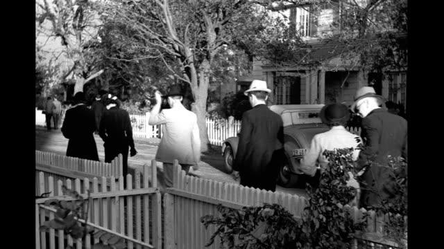 pedestrians men women children walking in small town past picket fence houses car pedestrians walking in small town on january 01 1940 - picket fence stock videos & royalty-free footage