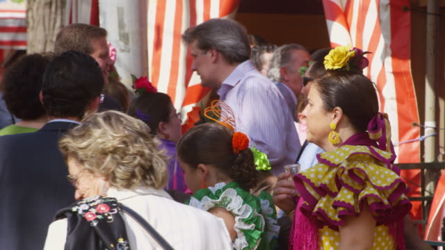 ms cu pedestrians mostly in traditional dress thronging on streets  / seville, andalusia, spain - flamenco dancing stock videos & royalty-free footage