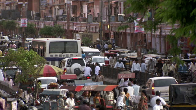 Pedestrians, motorcycles, and buses all maneuver through the busy streets of Jaipur, India. Available in HD