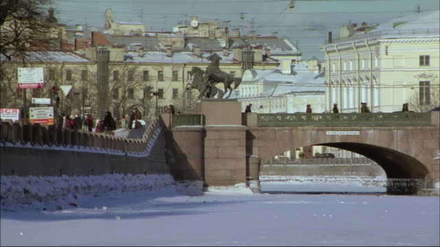 pedestrians move across a bridge spanning an icy river. - st. petersburg russia stock videos & royalty-free footage